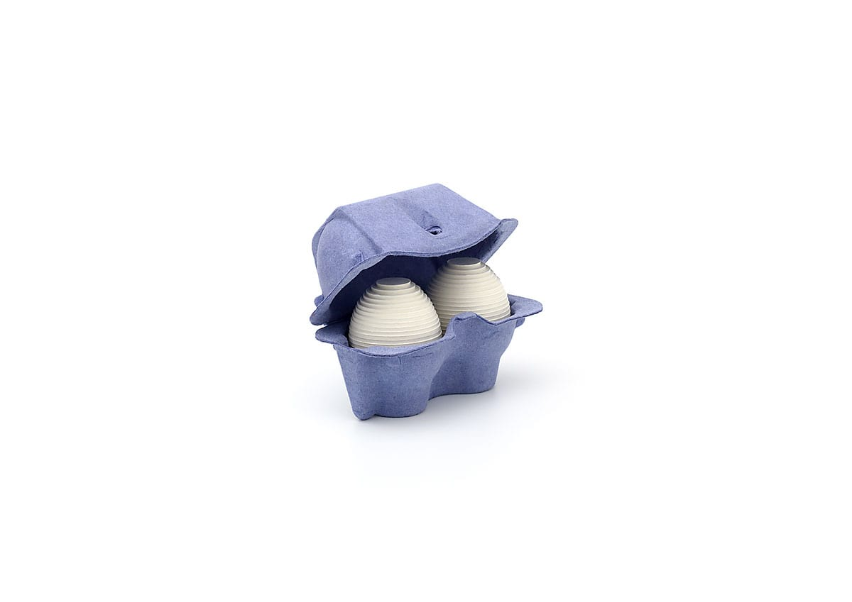 Fine art print of two layered white cardboard eggs in a deep blue two-egg paper pulp carton