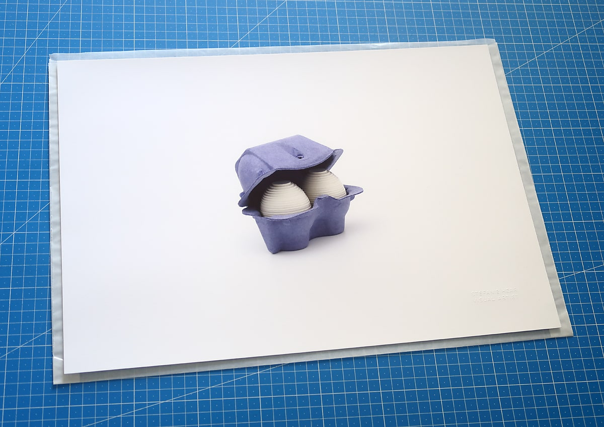 Limited edition print of two layered white cardboard eggs in a deep blue two-egg paper pulp carton