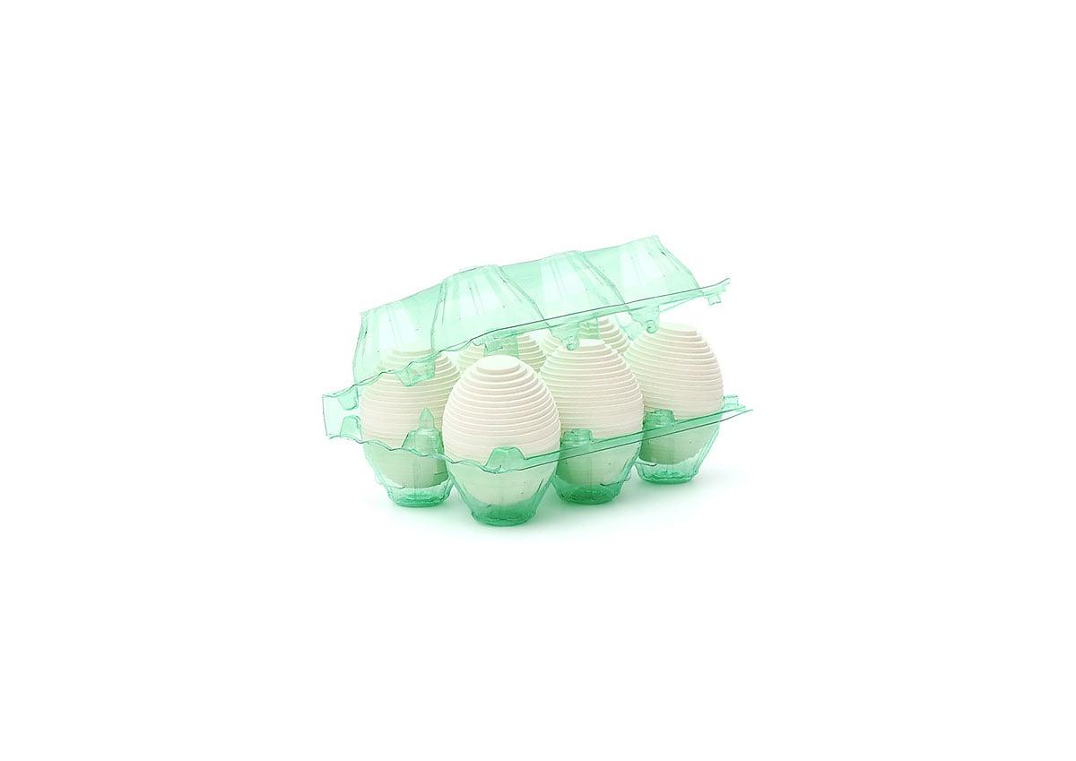 Fine art print of six layered white cardboard eggs in a clear green plastic six-egg carton