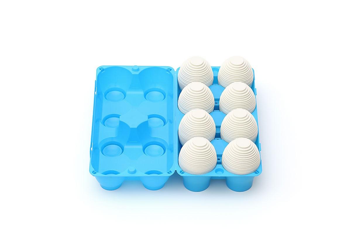 Fine art print of eight layered white cardboard eggs in a blue plastic eight-egg carton